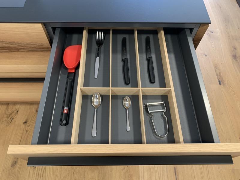 eine Küche von Späni AG Schreinerei und Innenausbau Schwyz, ausgerüstet mit Schublade mit dreiteiligem Besteckeinsatz